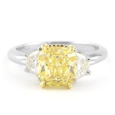 A modern twist on a timeless classic, this yellow and white diamond ring is sure to beguile even the most loyal of white diamond wearers. A 2.66 carat Fancy Intense Yellow cushion cut center diamond is flanked by two colorless half-moon shaped white diamonds. The crown is crafted in 18 karat yellow gold to showcase the center, and the remaining ring is completed in platinum.