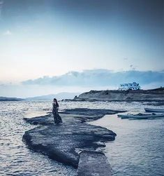 A woman in a long, flowy dress stands on rock surrounded by water. In the far background a greek home and in the water several small boats.  The sun is rising but its still dark.  Picture is taken in Polonia, Milos, Greece - Greece 7 day itinerary.