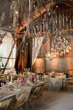 Some nice WEDDING DETAILS - using shawls as table cloths, the chandelier over the head table, the strings of crystals hanging from the ceiling, the twinkle lights on the rafters, the dried flower wreath over the head table - pretty BARN wedding #barn #wedding