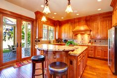 This bright and warm wood kitchen has a higher level bar area at one end of the kitchen island. Three pendant lights hang above it.