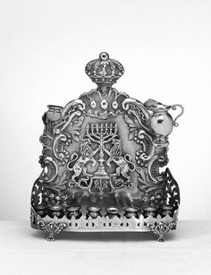 A RUSSIAN SILVER HANUKAH LAMP  St. Petersburg, 1892  The shaped rectangular back plate with arched and then crowned top, with chased borders of foliate scrolls, rocaille and flowers, centering applied lions of Judah flanked menorah, the platform applied with eight oil containers, with wick holder covers, with detachable servant light, and with a later oil pitcher--10in. (26.6cm.) high X 9in. (24 cm.) long, 28oz.