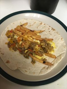 California Breakfast Burrito. Scrambled egg with salt, pepper, granulated garlic. I pickled mini peppers by boiling them in white vinegar then mixing them in with browned beef with a little beef broth. I threw in some shredded cheese to thicken the sauce. I refried McDonalds French fries. Assemble and add a little more cheese. Delish!