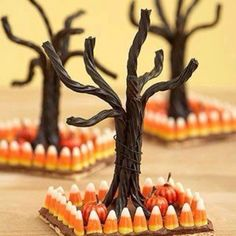 Cute edible Halloween decorations  Graham cracker covered with chocolate icing.  Candy corn placed around edge to form a fence.  Black licorice to pull apart & make a tree.  Place a few candy pumpkins around the tree.  Simple & cute.