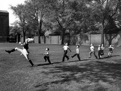 The drum major for the University of Michigan marching band high-steps as children follow suit, 1950.