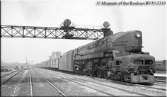 One of the PRR's stunning Class T-1 4-4-4-4 duplex-drive steam locomotives is seen here with a passenger train passing under the signal towe...