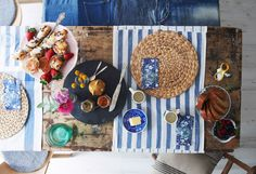 Striped towels as table runners and food on mismatched plates create a relaxed dining experience.