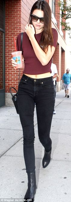 Statuesque: The television personality donned a midriff-revealing burgundy top and skinny black jeans tucked into a pair of leather boots