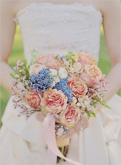 Vintage feeling peach and blue bridal bouquet. Love the tiny wax flowers and the brooch on her bouquet wrap. Image via Sparkle and Hay.