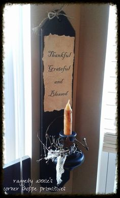 "Primitive Sconce/ Candle Holder in Black... wrapped in pip berries and cheesecloth.. accented with rusty stars and topped with a grubby candle. Home made label was torn and coffee stained for a vintage look and simply reads, ""Thankful, Grateful, Blessed""."