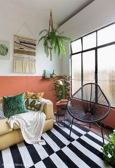 Meia parede pintada na cor ocre, sofá com almofadas estampadas, poltrona acapulco e muitas plantas nessa sala de estar.