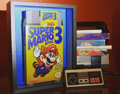 """Yesterday we posted a """"how to"""" link to our blog sharing how you can create your own shadow box inspired by your own childhood nostalgic memories. Today we're posting a photo of the final product for you.  Check out our blog at inspirednostalgia.com to check out our instructional post """"Project: Video Game Shadow Box."""" [Link in bio] #nes #shadowbox #nintendo #mariobros #videogames #blog #gamer #cartridge #supermariobros3 #nostalgic #memorymaking #childhood #memories #8bit #homedecor #retro…"""