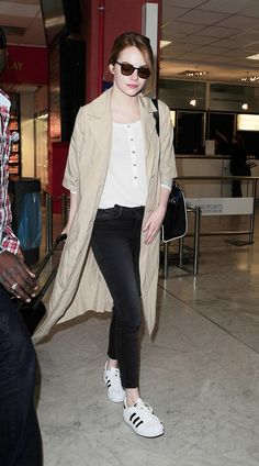 Emma Stone wears a white henley shirt with black ankle jeans, tennis shoe, a trench coat and sunglasses.