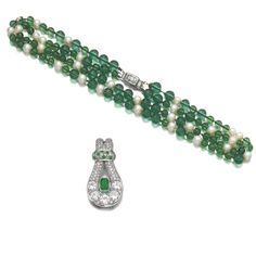 EMERALD AND DIAMOND CLIP, 1943 AND A CULTURED PEARL AND DIAMOND NECKLACE, SUZANNE BELPERRON, 1956 The clip set with a step-cut emerald withi...