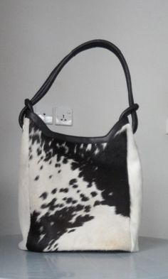 101665f5a Handmade black and white cowhide handbags perfect for your day to day use.  It comes with an adjustable strap, two pockets inside and leather bottom.