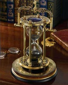 The Mariner's Hourglass   A striking detailed hourglass fashioned after those used to keep time for a ship's watch centuries ago. Made of precision die cast material and plated with 24 karat gold. Measures 9 inches in height.