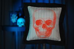 """Orange Skull Flanged Pillow from $30.00 A victorian skull illustration in Calvarium red™ rests on a field of stylish, tailored stripes. The back is solid black twill with an envelope closure.   Including the flange the pillow measures 17"""" x 17"""" and accommodates a 14"""" x 14"""" pillow insert (optional)."""