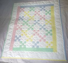 Her nine patch baby blanket (or quilt) is in great unisex colors including green, yellow, blue and pink, all over a white background. Description from etsy.com. I searched for this on bing.com/images