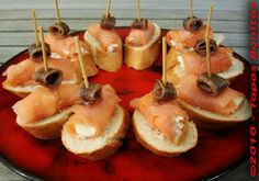 "Salmon with Smooth cottage cheese spread onto it and topped with an anchovy : known as ""Pinchos Salmon con Queso y Anchoa"""