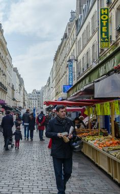 Rue Mouffetard, a Paris culinary market street with vendors selling fresh produce, cheese, fish, meat, pastries, and baked goods.