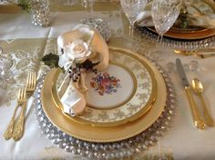 Dining Room- Place Setting, crystal and gold chargers with antique china cover plate trimmed napkin and rose. Gold German flatware, knife resting on an antique crystal knife rest.