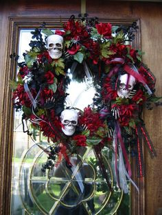 "OK, so I made it last year, but technically it is my ""most recent"" crafty project....Grapevine base, black and red silk flowers, some black chenille stems, styro skulls, little plastic skeletal hands, black spiders with silver paint, and all my scrap red/burgundy/white/silver/black ribbon On the big night I took it off the door and set it in the cemetery on a wreath stand (like an easel) next to a gravestone..."
