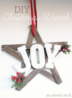 """Use stained wood, white lettering, and red garnishes to craft this Christmas """"joyful"""" wreath."""