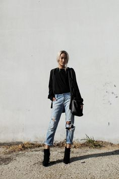 great outfit inspiration - torn boyfriend jeans and a black top with black booties