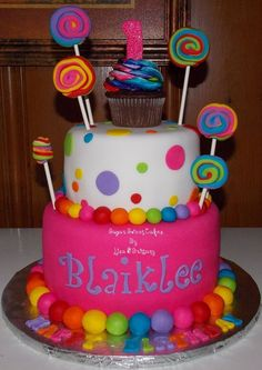 6 8 cakes iced in fondant w/hand made fondant lollipops. The cupcake on top was iced in buttercream w/a rainbow swirl will be used as the smash cake. TFL! :)