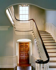 Wonderful, sweeping staircase, perfectly punctuated in white and walnut. Turquoise walls, crisp millwork and a walnut door