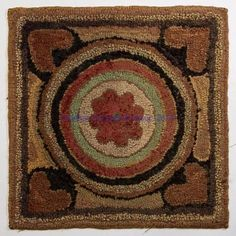 """AMERICAN FOLK ART HOOKED MAT, wool and cotton on burlap, a charming example, featuring a floral device centered by concentric circles and framed by four hearts in the corners. Circa 1880-1900. 15"""" x 15 1/2""""."""