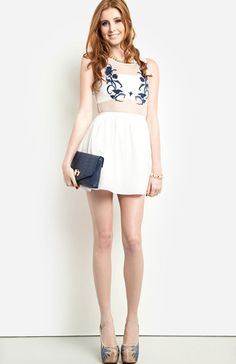 TARLET SENSATION This crisp white fit and flare dress is perfect for a summer soirée with a mini hemline, mesh bodice, and contrasting floral embroidery. Rhinestone accents from the gold jewelry and stunning statement heels amplify this extraordinary ensemble.