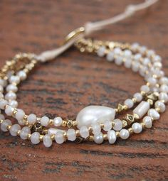 Triple strands Bracelet made with Freshwater pearl, Crystal, White jade and Gold plated Nuggets. {{ Product Detail }} ✧ Length : 16cm with adjustable. ✧ Closure : Button PLEASE NOTE : The handcrafted nature of this product will produce minor differences in design, sizing and weight. Variations will occur from piece to piece, measurements may vary slightly PLEASE NOTE : The handcrafted nature of this product will produce minor differences in design, sizing and weight. Variations will occur…