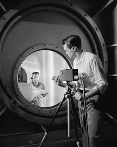 A television camera is focused by NACA technician on a ramjet engine model through the schlieren optical windows of the 10 x 10 Foot Supersonic Wind Tunnel's test section. Closed-circuit television enables aeronautical research scientists to view the ramjet, used for propelling missiles, while the wind tunnel is operating at speeds from 1500 to 2500 mph