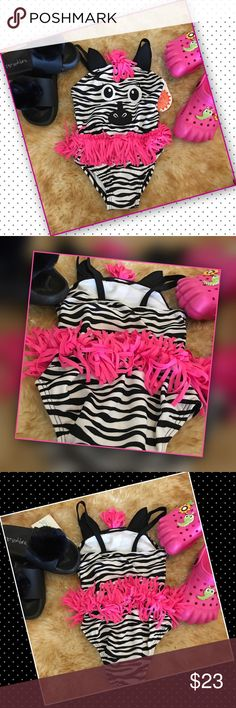 "Zebra Face For the love of the wild this one piece is full of zebra fun. Whimsical zebra face, zebra design, with hot pink fringe trim. Summer time will be wild and fun at the beach, pool, or party. UPF 50+. 88% polyester 12% spandex. Lining 100% polyester. Company size chart 2T, 31-33"" height, 25-27.5 LBS. Fun Fashion For Your Little One. Swim One Piece"