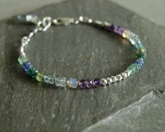 This multi gemstone bracelet is made with a blissful assortment of small genuine blue green gemstones such as Columbian emeralds, Zambian emeralds, Ethiopian opals, tanzanite, amethyst and aquamarine, apatite and peridot, with small sterling beads in between. In the center of this multi-gemstone feminine bracelet are small faceted sterling beads. This blue green jewelry bracelet closes with a sterling silver lobster clasp, and has a beautiful emerald briolette and violet tanzanite hanging by…