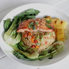 Miso glazed salmon served over vegetable fried brown rice with grilled baby bok choy and pineapple.