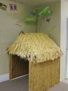 hut-- cardboard with roof made from faux grass skirts. walls covered with plastic tablecloth with bamboo print?grass hut-- cardboard with roof made from faux grass skirts. walls covered with plastic tablecloth with bamboo print?