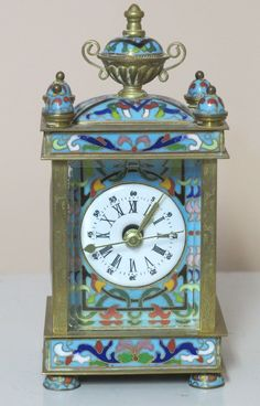 A 20th Century diminutive champleve enameled bronze clock. The rectangular footed case mounted with a twin handled urn finial. The side panels with enameled portraits depicting a young beauty. Black and white enameled dial.  NOTE: The works replaced with a quartz battery.