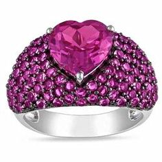 This stylish ring features a large heart-cut created pink sapphire center stone encircled by round-cut created pink sapphire gemstones. Crafted of sterling silver, this elegant ring shines with a high