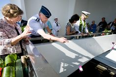 USS Arizona Memorial.  General Gary L. North, Commander Pacific Air Forces PACAF (left) and Admiral Patrick M. Walsh, Commander US Pacific Fleet USN (center right) and their wives toss ceremonial flowers into the water symbolizing the 1,177 USS Arizona crewmen who lost their lives on December 7, 1941.