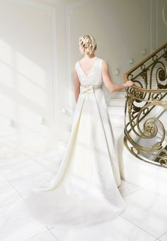 mona berg Kollektion 2015 - Lilie; Modernes Brautkleid aus Satin mit Drapagen, V-Ausschnitt und eleganter Applikation und lässigen Nahttaschen. Die atemberaubende Schleppe ist abnehmbar. Foto: Svea Ingwersen