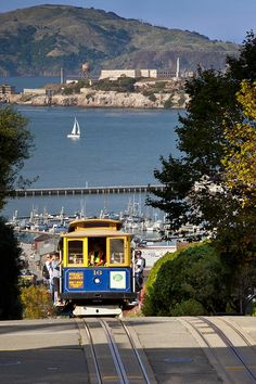☀San Francisco cable car runs up Hyde Street above the bay and Alcatraz Prison beyond, California, USA,  by Brian Jannsen