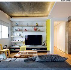 Na sala com teto e vigas de concreto bruto aparente, o estúdio Superlimão criou uma iluminação com lâmpadas fluorescentes embutidas nos rebaixos de gesso acartonado que lembram sancas.