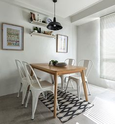 The dining area is furnished with a simple wooden table and metal dining chairs on a geometric-print floor rug. To help save on the precious floor area, the interior designer set the pieces against the wall.