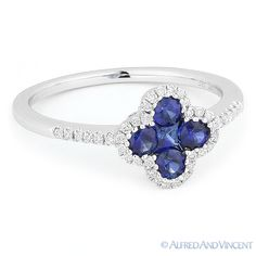 The featured ring is cast in 14k white gold and showcases a flower design set with a princess cut blue sapphire center, round cut blue sapphire petals, & round cut diamond accents set along the flower outline and on both sides of the band.