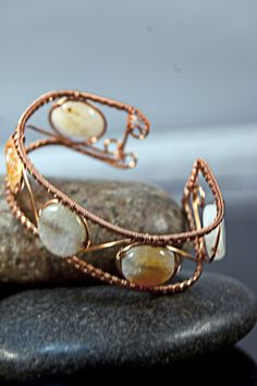 These lovely light blue and sun kissed orange 16 mm Sun Agate disks are fashioned into a 24 mm (1 inch) wide bracelet made from sealed wire woven copper wire. A four/four weave forms a frame around th