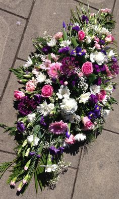 Casket spray, pinks, white and purples. Funeral tribute. Butterflies and Blooms UK