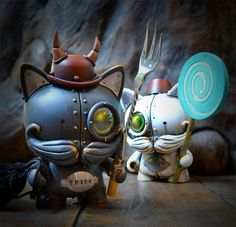 UK's notorious steampunk artisan, Doktor A, has just posted an eerie shot of a new custom set cleverly titled Trick and Treat. Standing 5-inches tall, this pair of mustachioed TRIKKY customs were created using vinyl, rubber, lead, epoxy resin, polymer clay, brass vintage clockwork keys and vintage silver trident. The dapper duo is set to show in the upcoming Halloween exhibition, Bewitching, at Stranger Factory this October.