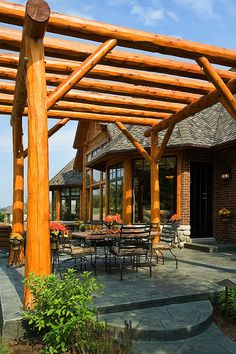 Log pergola shelters the outdoor entertainment area.