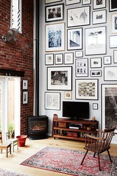 Mostly black and white gallery wall decor in a living room design. An eclectic gallery wall of framed neutral photos and artwork all the way up to the ceiling - Art Wall Decor & Layout